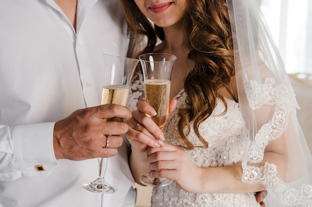 De bruid en bruidegom drinken champagne. pasgetrouwden met een bril.