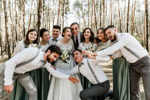 De bruid en bruidegom en hun vrienden hebben plezier en knuffelen