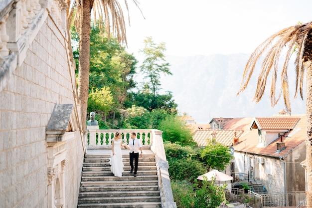De bruid en bruidegom gaan de oude trappen af van de geboorte van de kerk van de heilige maagd maria
