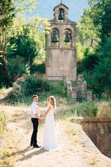 De bruid en bruidegom houden elkaars hand vast bij de oude klokkentoren bij de kerk in prcanj