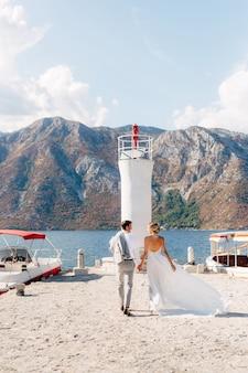 De bruid en bruidegom houden elkaars hand vast langs de pier naar de vuurtoren in de baai van kotor