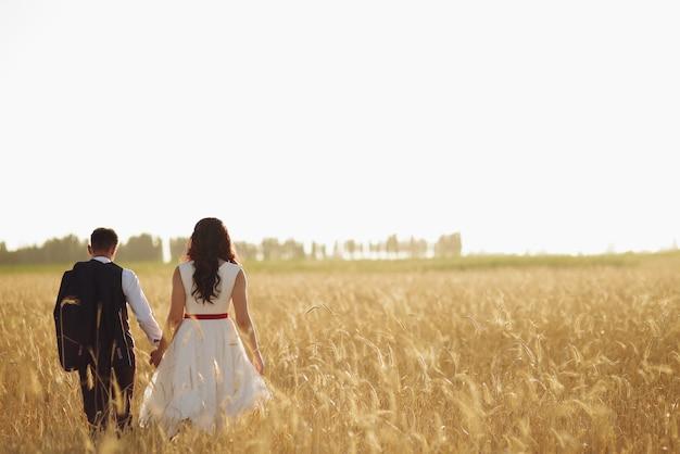 De bruid en bruidegom houden elkaars hand vast, omhelzen elkaar en wandelen in het park.