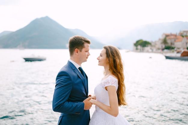 De bruid en bruidegom houden elkaars hand vast op de pier in perast, achter hen vaart een boot