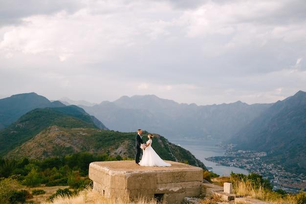 De bruid en bruidegom houden elkaars hand vast op het dak van het fort van gorazda, achter hen met uitzicht op de baai