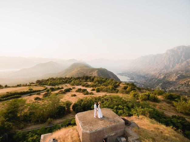 De bruid en bruidegom houden elkaars hand vast op het dak van het gorazda-fort, achter hen een uitzicht op de baai van kotor