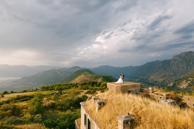 De bruid en bruidegom houden elkaars hand vast op het dak van het gorazda-fort