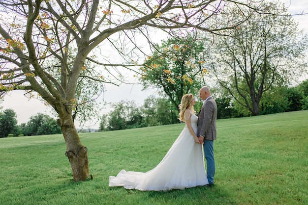 De bruid en bruidegom houden elkaars handen vast. een man en een vrouw kijken elkaar in de ogen.