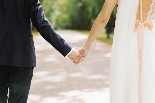 De bruid en bruidegom houden elkaars handen vast. liefhebbend stel