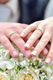 De bruid en bruidegom houden handen met trouwringen op het boeket