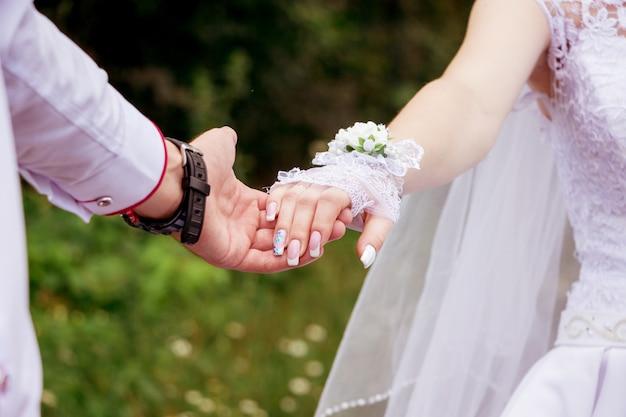 De bruid en bruidegom houden voor handen. eenheid van twee geliefden