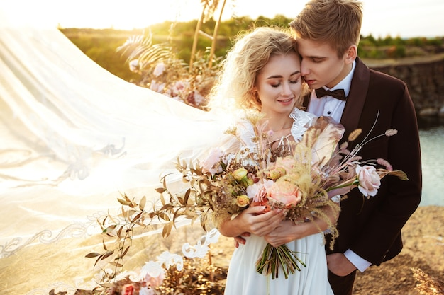 De bruid en bruidegom in de buurt van de bruiloft decoratie tijdens een ceremonie op een rots in de buurt van het water bij zonsondergang. sluier die uit de wind vliegt