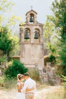 De bruid en bruidegom in kransen knuffelen bij de oude klokkentoren bij de kerk in prcanj