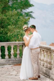 De bruid en bruidegom in kransen omhelzen elkaar teder