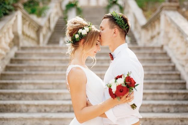 De bruid en bruidegom in kransen staan knuffelend en kussend op de trap