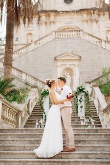 De bruid en bruidegom in kransen staan knuffelend op de trap