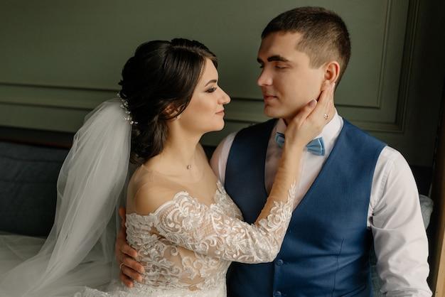 De bruid en bruidegom kijken elkaar aan en omhelzen elkaar. mooie elegante paar pasgetrouwden verliefd in een loft interieur. bruiloft concept.