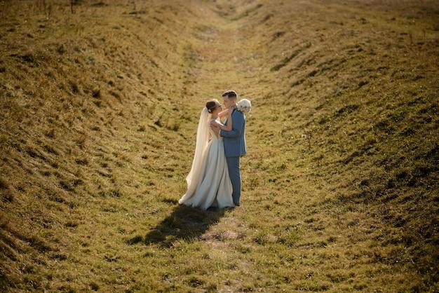 De bruid en bruidegom kijken elkaar in de ogen. herfst bruiloft fotoshoot. pra ligt in een diep ravijn.