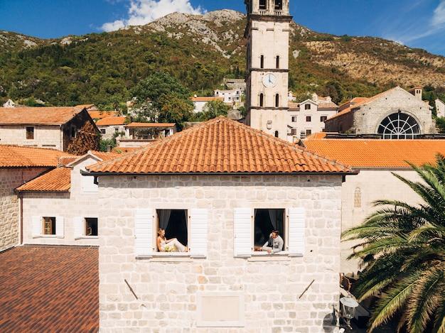 De bruid en bruidegom kijken uit de nabijgelegen ramen van een bakstenen huis met een oranje dak in het oude