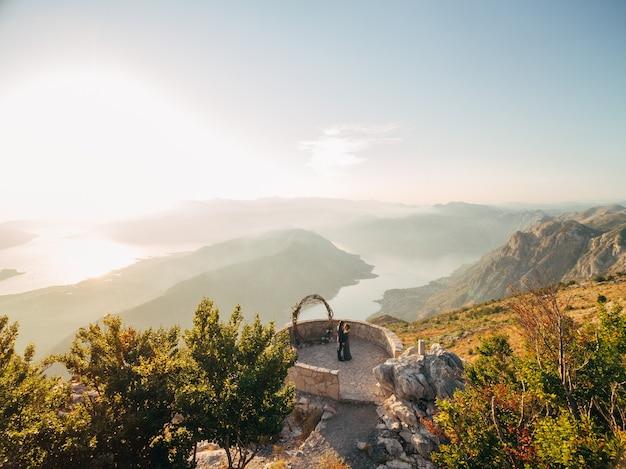 De bruid en bruidegom knuffelen bij de huwelijksboog op het observatiedek op de berg lovcen met uitzicht op de baai van kotor