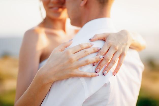 De bruid en bruidegom knuffelen buitenshuis