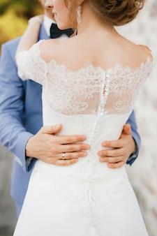 De bruid en bruidegom knuffelen de bruidegoms handen op de taille van de bruid in een close-up van een kanten jurk