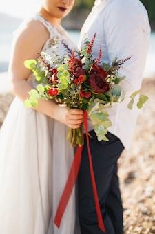 De bruid en bruidegom knuffelen en houden een bruidsboeket vast op het kiezelstrand aan zee