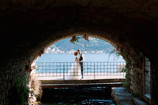 De bruid en bruidegom knuffelen en kussen op de brug onder de boog achter hen is de baai van kotor