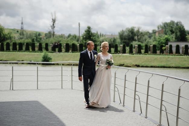De bruid en bruidegom knuffelen en lopen samen