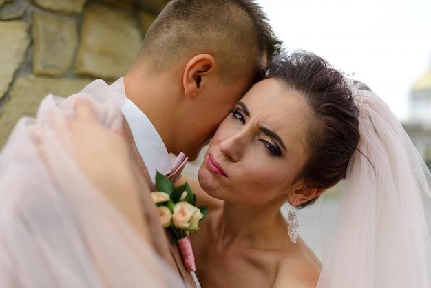De bruid en bruidegom knuffelen. focus op de bruid. een vrouw kijkt in het frame. het meisje knipoogt. close-up shot.