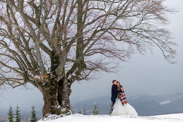 De bruid en bruidegom knuffelen onder een kleed om warm te blijven. winter bruiloft