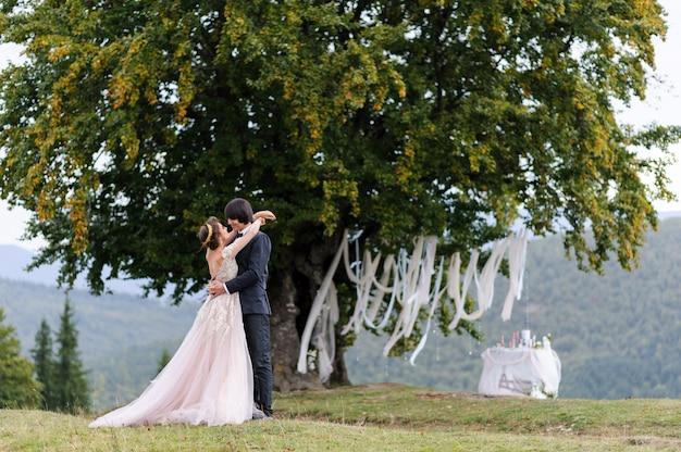 De bruid en bruidegom knuffelen onder een oude eik. bruiloft fotoshoot in de bergen.