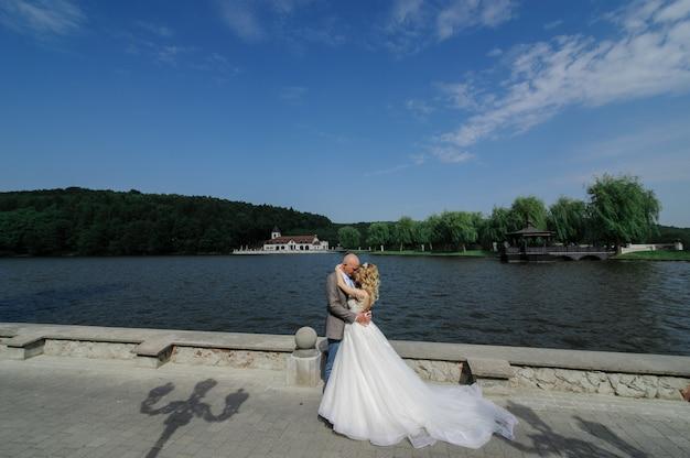 De bruid en bruidegom knuffelen op de achtergrond van het meer. man en vrouw kijken elkaar in de ogen.