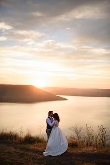 De bruid en bruidegom knuffelen op de achtergrond van het meer tijdens zonsondergang