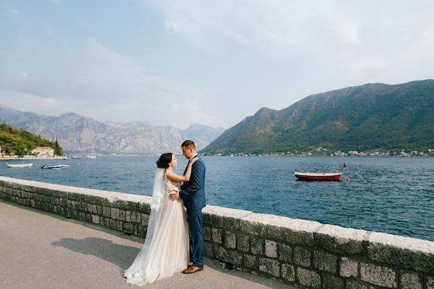 De bruid en bruidegom knuffelen op de pier in de buurt van de oude binnenstad van perast