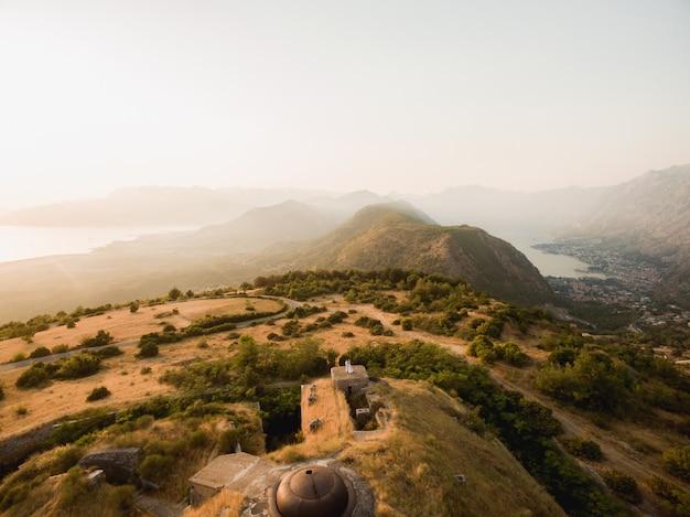 De bruid en bruidegom knuffelen op het dak van het gorazda-fort met achter hen een uitzicht op de baai van kotor