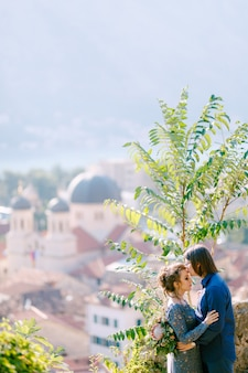 De bruid en bruidegom knuffelen op het observatiedek met een schilderachtig uitzicht op de oude binnenstad van kotor, close-up