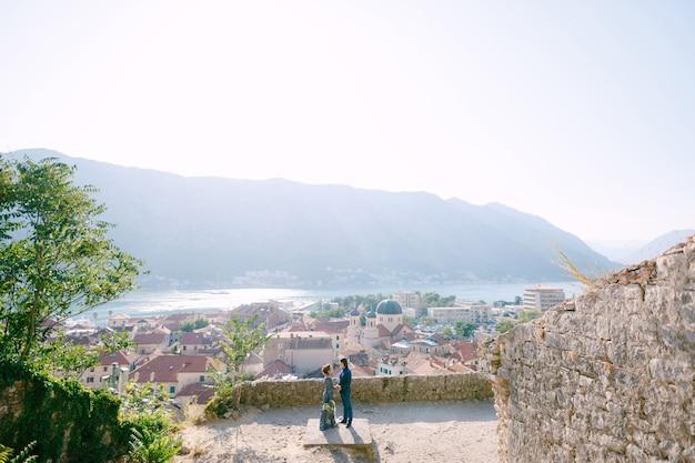 De bruid en bruidegom knuffelen op het observatiedek met een schilderachtig uitzicht op de oude binnenstad van kotor en