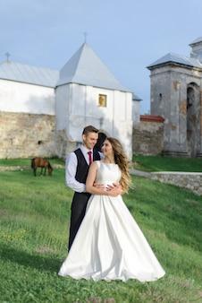 De bruid en bruidegom knuffelen op het oude klooster.