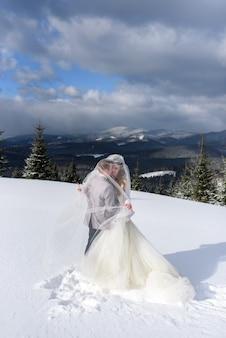 De bruid en bruidegom knuffelen tijdens het wandelen onder de sluier. winter bruiloft. even voor de kus.
