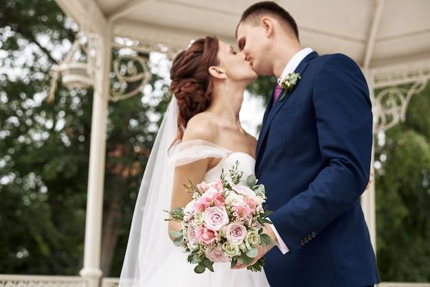 De bruid en bruidegom kussen in de open lucht. focus op het boeket. bruiloft, liefde en jeugdconcept.