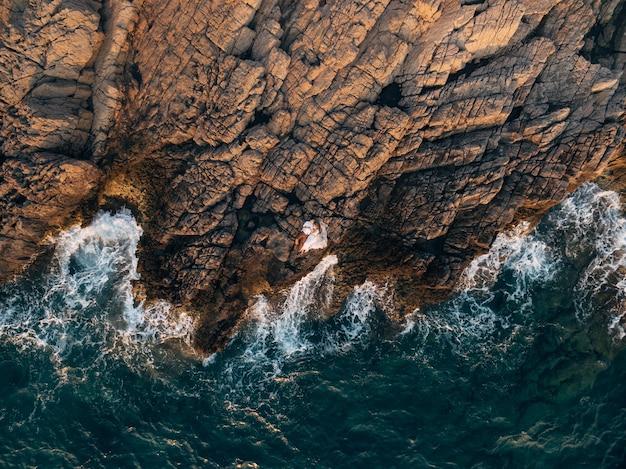 De bruid en bruidegom lagen knuffelend op de rotsen bij het bovenaanzicht van de zee