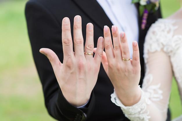 De bruid en bruidegom laten hun trouwringen zien