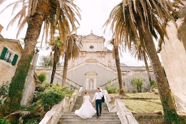 De bruid en bruidegom lopen de trap af van de geboorte van de kerk van de heilige maagd maria