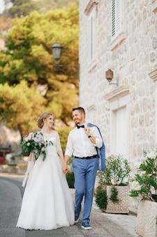 De bruid en bruidegom lopen hand in hand in de buurt van een prachtig bakstenen huis in het oude centrum van perast