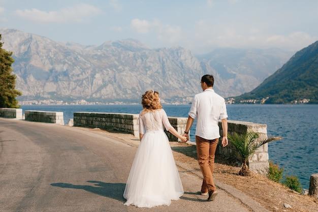 De bruid en bruidegom lopen hand in hand langs de weg langs de kust in de baai van kotor bij perast