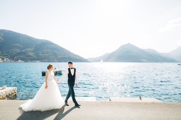 De bruid en bruidegom lopen hand in hand over de weg langs de zee achter hen zijn bergen en een