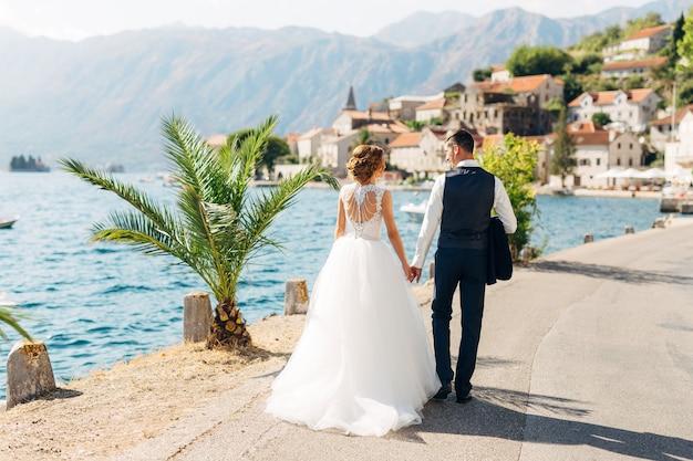 De bruid en bruidegom lopen hand in hand over de weg langs de zee bij het oude centrum van perast terug