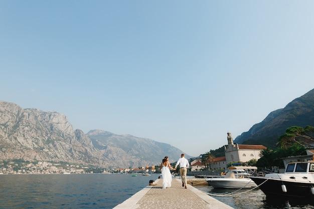 De bruid en bruidegom lopen langs de pier in de baai van kotor in de buurt van de oude stad en het houden van boten