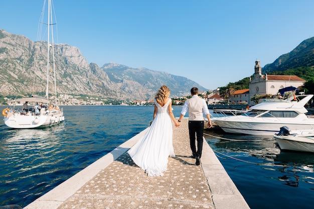 De bruid en bruidegom lopen langs de pier in de baai van kotor, naast hen liggen boten, jachten
