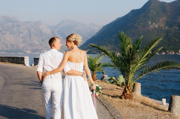 De bruid en bruidegom lopen langs de pier in de buurt van het oude centrum van perast en knuffelen elkaar achteraanzicht